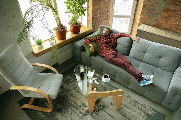 Homme restant à la maison, assis sur le canapé