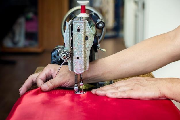 Un homme reste à la maison couture tissu rouge, c'est passe-temps, machine à coudre d'occasion, gros plan