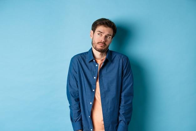 Homme réticent et triste se sentant bouleversé, regardant de côté un espace vide avec un visage non amusé, debout sur fond bleu.