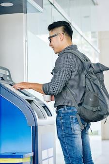 Homme retirant de l'argent du terminal bancaire