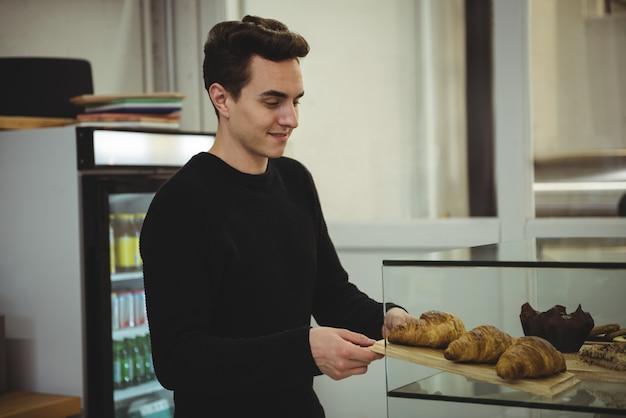 Homme retirant le plateau de croissants