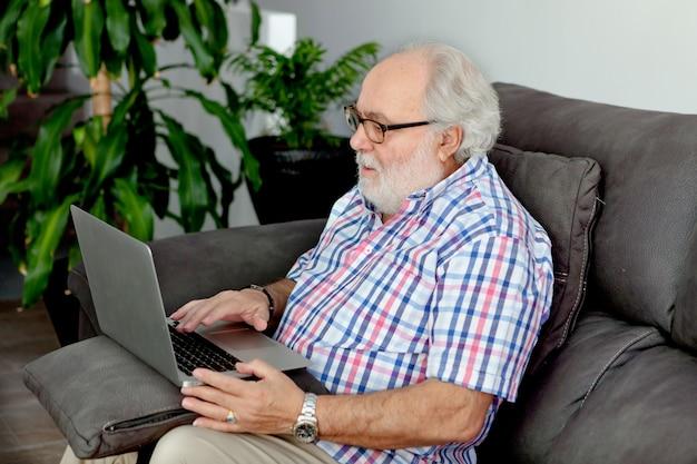 Homme à la retraite avec une barbe blanche assis chez lui