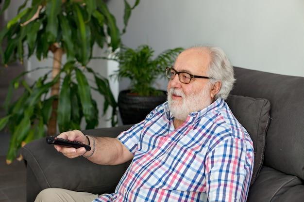 Homme à la retraite avec une barbe blanche devant la télé