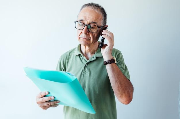 Homme retraité entrepreneur vêtu d'une chemise verte et des lunettes, lisant un dossier avec un rapport et parlant au mobile
