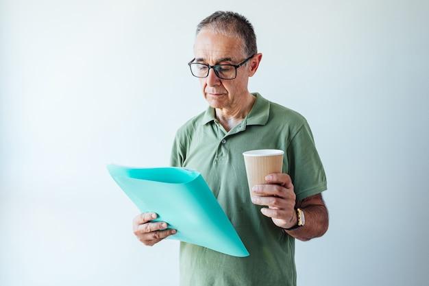 Homme à la retraite entrepreneur vêtu d'une chemise verte et des lunettes, tenant un dossier avec un rapport et un café