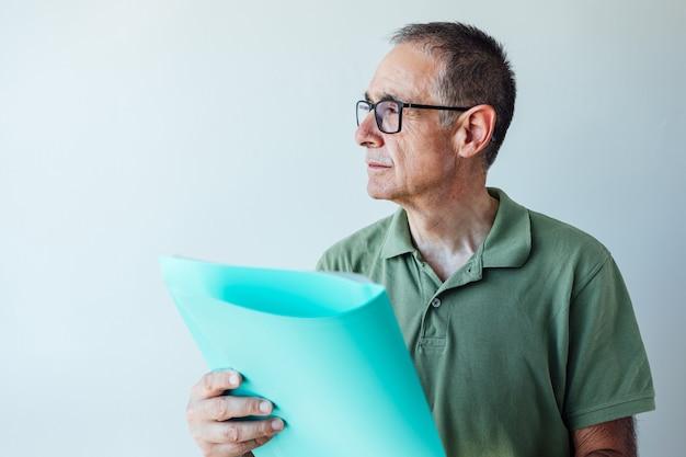Homme retraité entrepreneur vêtu d'une chemise verte et des lunettes, tenant un dossier avec un rapport