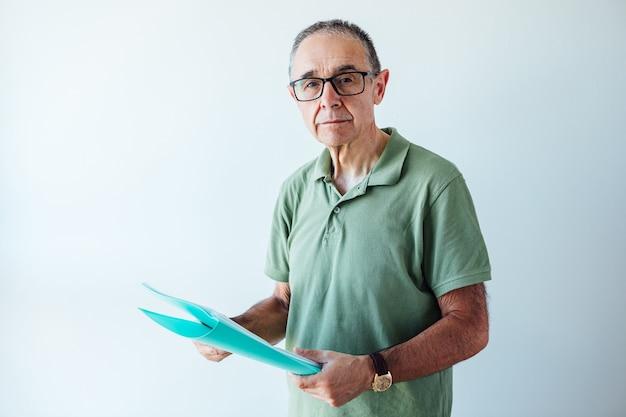 Homme retraité entrepreneur vêtu d'un polo vert tenant un dossier avec un rapport regardant la caméra