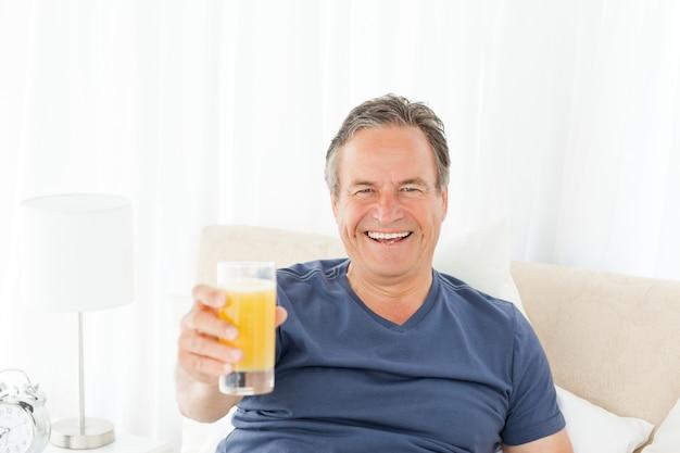 Homme à la retraite en regardant la caméra pendant qu'il boit du jus d'oranje
