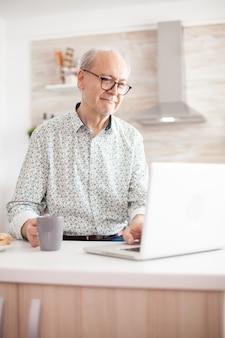 Homme retraité senior aux cheveux gris naviguant sur internet. vie quotidienne d'un homme âgé dans la cuisine pendant le petit-déjeuner à l'aide d'un ordinateur portable tenant une tasse de café. personne âgée à la retraite travaillant à domicile, télétravaillant u