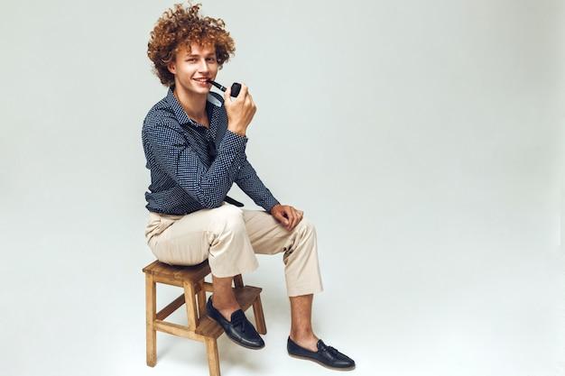 Homme rétro positif habillé en chemise assis et posant