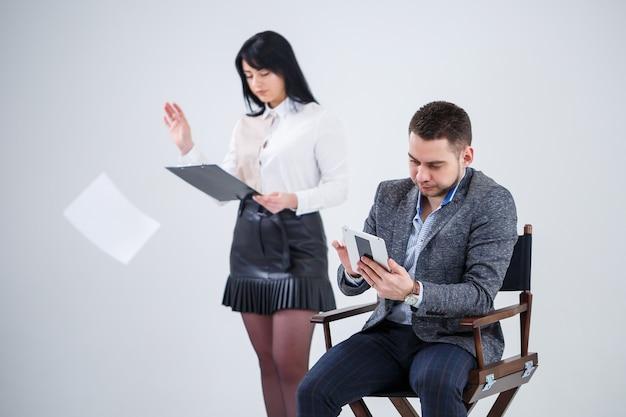 Un homme réussi en costume est assis sur une chaise noire avec une tablette et une femme jette des documents. les futurs hommes d'affaires sont nerveux et parlent d'un nouveau projet. partenaires commerciaux sur fond blanc.
