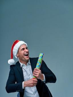 L'homme réussi dans un costume sur un fond gris dans un chapeau du père noël célèbre le nouvel an. prise de vue en studio.