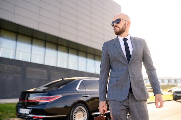 Homme réussi dans un costume avec une mallette sur le fond d'une voiture chère
