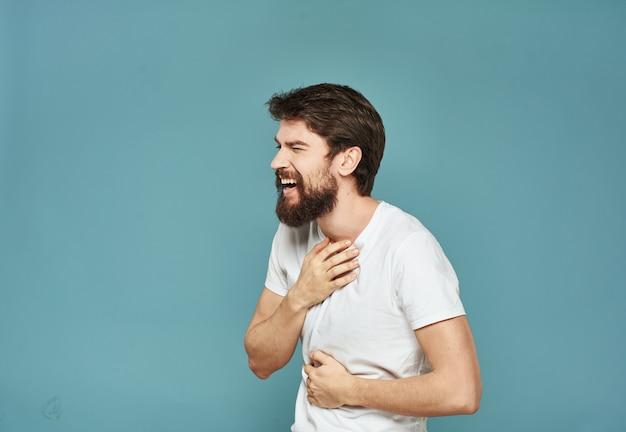 Un homme réussi dans un t-shirt blanc a serré ses mains dans un poing sur un fond bleu