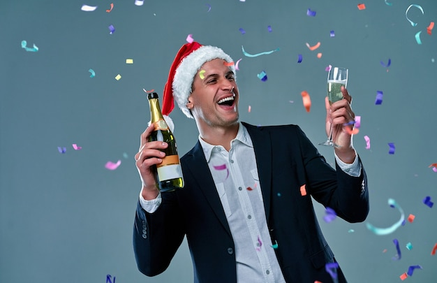 L'homme réussi dans une veste avec une bouteille de champagne et un verre célèbre le nouvel an. photo en studio sur fond gris avec des confettis.