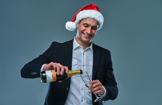 Un homme réussi dans une veste et un chapeau de noël verse du champagne dans un verre pour fêter le nouvel an. photo studio sur fond gris.