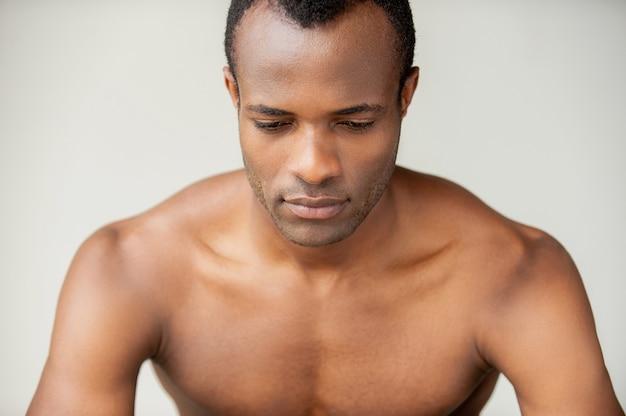Homme rêvant. beau jeune homme musclé regardant vers le bas en se tenant debout sur fond gris