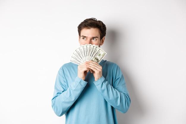Homme rêveur pensant à acheter un produit, détenant de l'argent et regardant à gauche, pensif, faisant du shopping, debout sur fond blanc