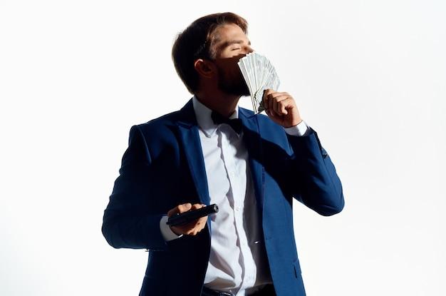 Homme riche avec pistolet et liasse d'argent costume classique fond blanc.
