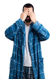 Homme en robe de chambre couvrant ses yeux