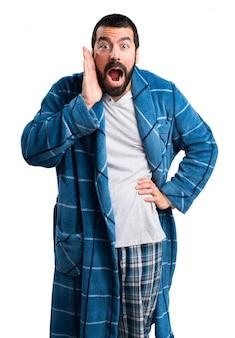 Homme en robe de chambre faisant un geste de surprise