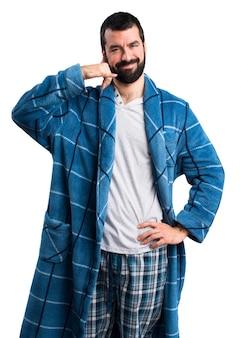 Homme en robe de chambre faisant un geste téléphonique