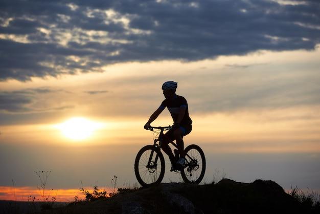 Homme robuste et fort portant des vêtements de sport et un casque assis sur son vélo et posant sur la colline. cycliste bénéficiant d'une vue magnifique sur le coucher du soleil. concept de motivation, de loisirs et d'activités saines.