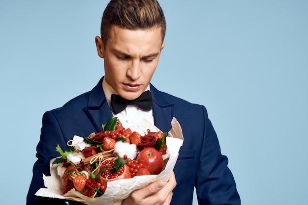 Homme romantique avec un bouquet de fleurs et dans un nœud papillon sur un bleu