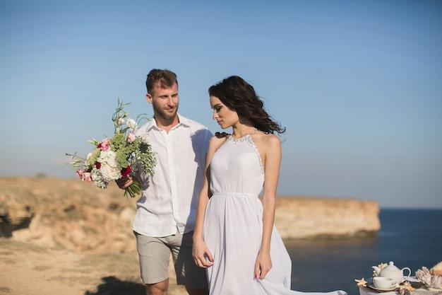 Homme romantique donnant des fleurs à sa petite amie dans la nature.