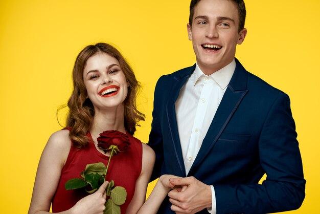 Un homme romantique embrasse une femme dans une robe rouge avec une rose à la main sur un fond jaune.