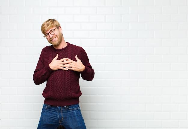 Homme romantique, heureux et amoureux, souriant joyeusement et tenant la main près du cœur