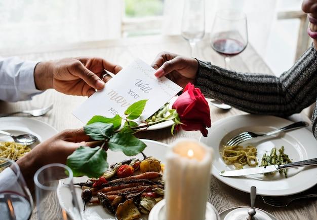 L'homme romantique qui donne va m'épouser carte avec une rose pour proposer la femme