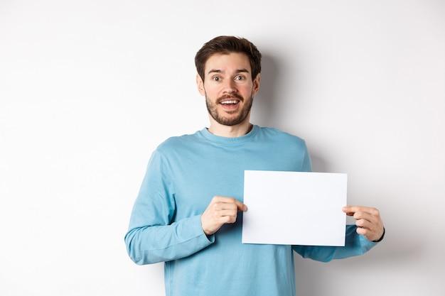 Homme romantique à la recherche d'un visage plein d'espoir à la caméra, montrant une carte de signe, un morceau de papier vierge pour une bannière ou un logo, debout sur fond blanc.