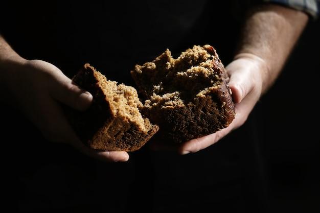 L'homme rompre le morceau de pain sur fond sombre, gros plan