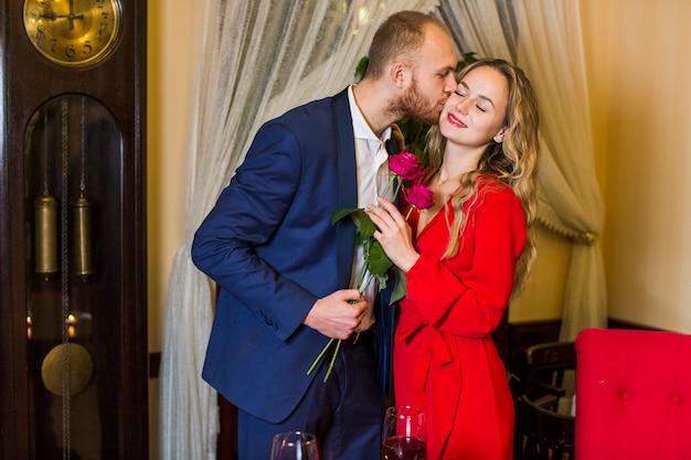 Homme avec des roses, embrassant une femme sur la joue au restaurant