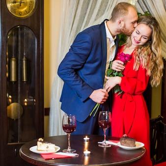Homme avec des roses s'embrasser une jolie femme sur la joue au restaurant