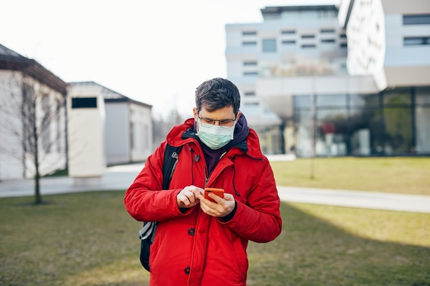 Homme en rouge et avec un masque de protection à l'aide de son téléphone dans la rue tout en covid19, mec à lunettes avec smartpone marche en plein air en protecteur de visage