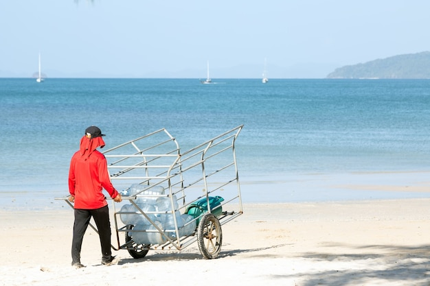 L'homme en rouge porte un chariot en fer avec des bidons d'eau vides sur la plagelivraison d'eau à l'île par bateauxdiy