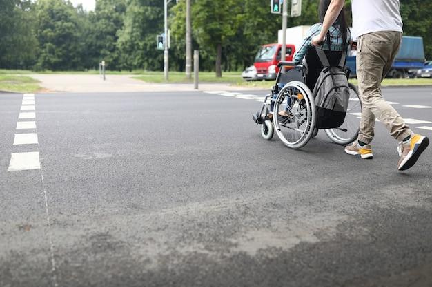 L'homme roule la femme en fauteuil roulant à travers la route.