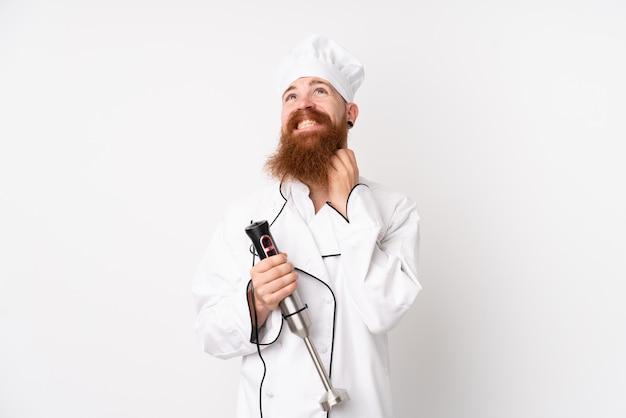 Homme rousse à l'aide d'un mélangeur à main sur un mur blanc isolé en pensant à une idée