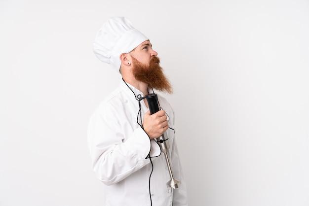 Homme rousse à l'aide d'un mélangeur à main sur un mur blanc isolé à la recherche de côté