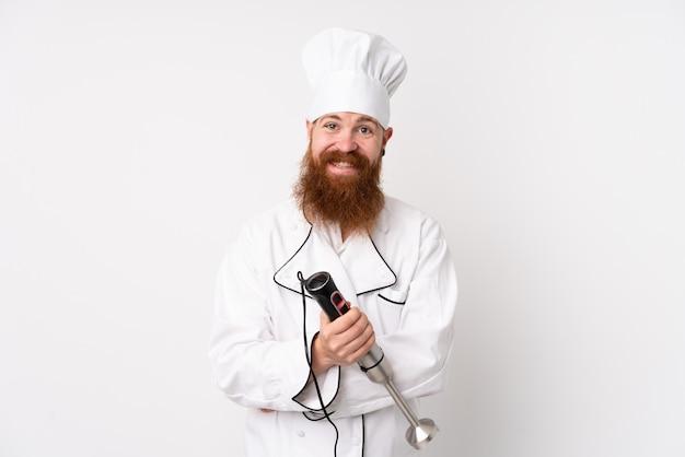 Homme rousse à l'aide d'un mélangeur à main sur un mur blanc isolé en riant