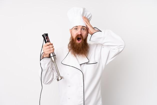 Homme rousse à l'aide d'un mélangeur à main sur un mur blanc isolé surpris et pointant le doigt sur le côté