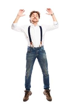Un homme rousse assez souriant avec une barbe en jean et une chemise blanche saute. isolé sur mur blanc. verticale.