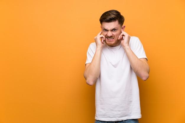 Homme rousse au mur marron frustré et couvrant les oreilles