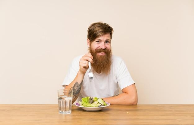 Homme rousse à la barbe longue et à la salade souriant