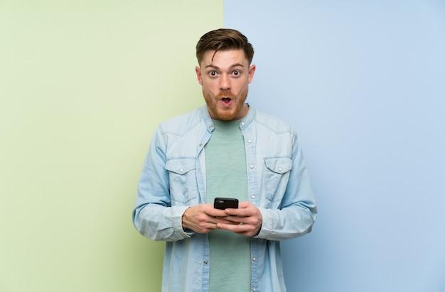 Homme rousse coloré sur surpris et envoyant un message