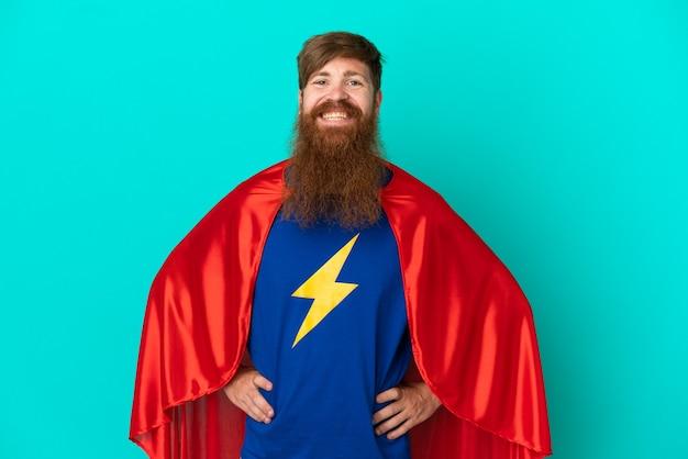 Homme rousse en costume de super-héros posant avec les bras à la hanche et souriant