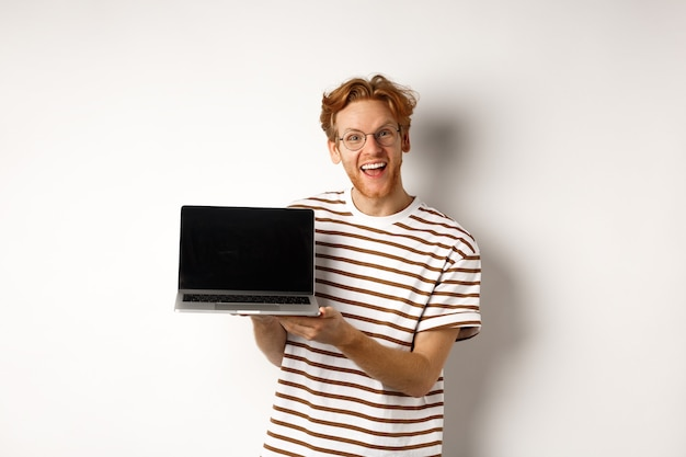 Homme rousse drôle dans des verres montrant la publicité sur l'écran de l'ordinateur portable et souriant. guy aux cheveux rouges démontre une promo ou une bannière sur écran, fond blanc.