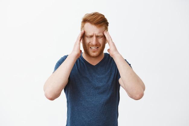 Homme rousse entrepreneur aux cheveux rouges touchant les tempes fronçant les sourcils et grimaçant de maux de tête douloureux, de maux de tête ou de migraine